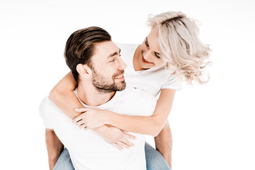 Handsome young adult man giving piggyback to wonderful blonde woman isolated on white