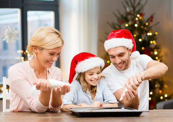 food, family and holidays concept - happy mother, father and daughter family in santa hats decorating bakery by pastry bags with frosting over christmas tree lights background