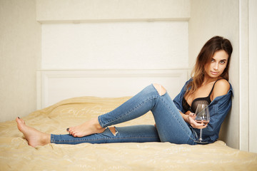 Young woman wearing jeans on bed with glass of wine, shallow depht of field