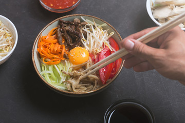 Traditional Asian Bibimbap dish with rice and vegetables on dark background. Man takes the dish using chopsticks