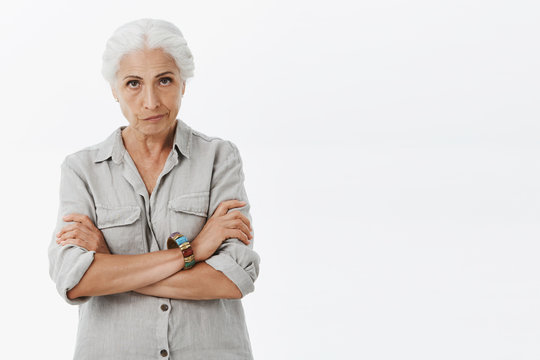 I need explanations young lady. Displeased angry elderly mother with grey hair looking from under forehead with irritated expression pursing lips crossing arms over chest scolding granddaughter