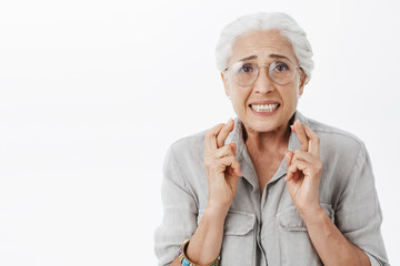 Anxious and concerned hopeful silly senior woman in glasses with white hair crossing fingers for good luck frowning looking intense waiting for impotant news nervously against gray wall