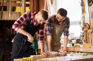 profession, carpentry, woodwork and people concept - two carpenters with electric drill drilling wooden board at workshop