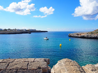 view across the bay in cala santandria menorca with old military ruins looking out on to bright blue sea