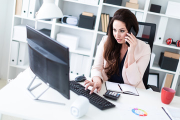 A young girl sitting at a table in the office, talking on the phone and working at the computer.