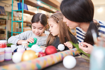 Portrait of two little kids making Christmas decorations in crafting class with smiling female teacher