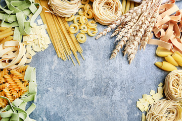 Mixed types and shapes of italian pasta on grey stone, background