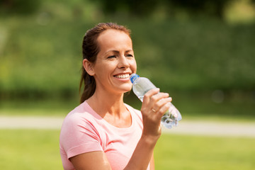 fitness, sport and healthy lifestyle concept - woman drinking water after exercising in park