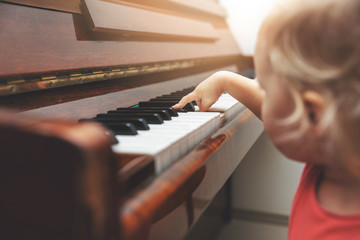 music education - child pushing piano keys