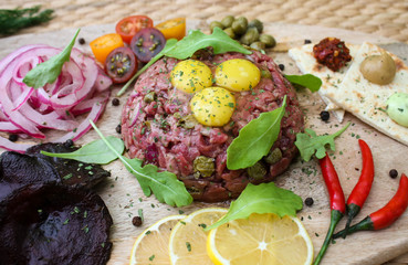 Beef tartare with quail eggs, capers and various appetizers