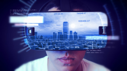 Young man wearing VR headset and watching business and economy related graphics.