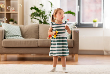 childhood and family concept - little girl blowing soap bubbles at home