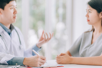 Physician in medical practice with patients. Conversation and advice of the treatment and medical costs.