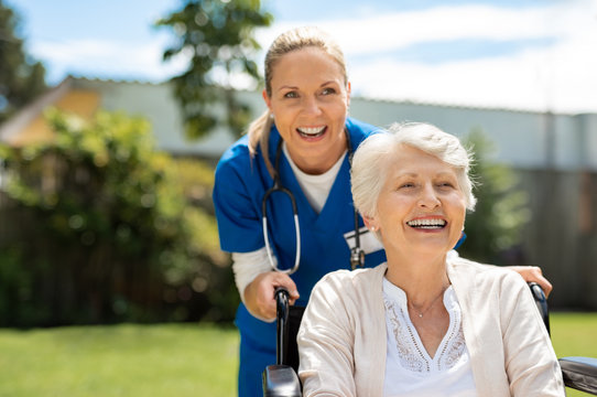 Woman on wheelchair having fun with nurse