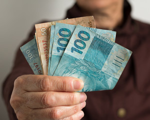Paper notes from Brazil. Front view senior person holding bills.