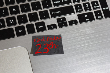 Advert message of Black friday on post it: reminder on laptop.