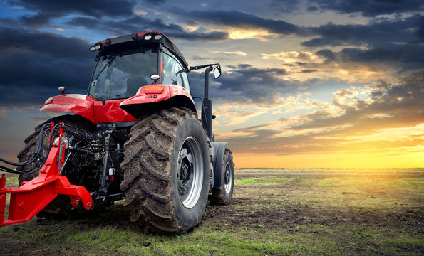 Agricultural tractor working in the field at sunset background