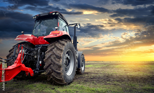 Wall mural Agricultural tractor working in the field at sunset background