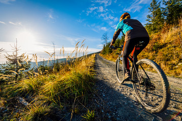 Cycling woman riding on bike in autumn mountains forest landscape. Woman cycling MTB flow trail track. Outdoor sport activity. Fototapete