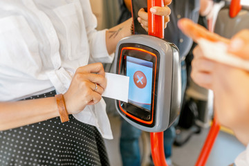 Woman trying to validate electronic ticket in public transport and machine denial to read ticket