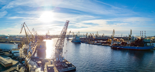 Aerial; drone view of port with shipyard silhouettes on the horizon; industrial cityscape in sunny weather with blue sky; process of ship repairing, logistic import export and transport background Fototapete