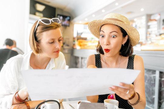 Shocked and surprised girlfriend girlfriend looking at the menu in the restaurant