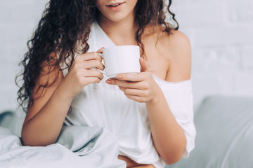 partial view of woman drinking coffee in bed during morning time at home