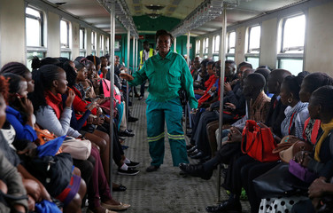 A train conductor walks inside a carriage as passengers ride inside a Nairobi Commuter Rail Service (NCRS) train from the Mutindwa station in Nairobi