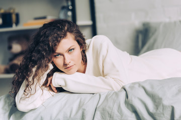 selective focus of beautiful curly woman looking at camera in bed at home