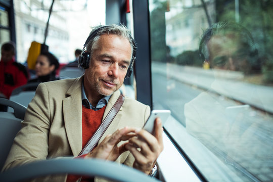Mature tired businessman with heaphones and smartphone travelling by bus in city.