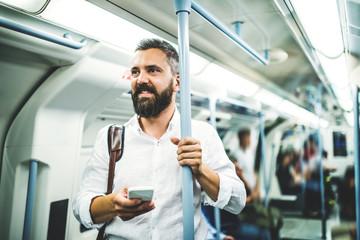 Hipster businessman with smartphone inside the subway in the city, travelling to work. Wall mural