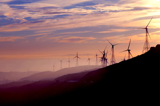 Wind turbines silhouettes. Environment friendly, alternative renewable energy concept. Sunset and ocean on the background.