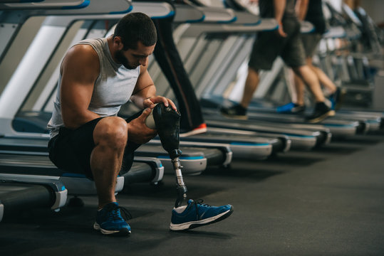 exhausted young sportsman with artificial leg sitting on treadmill at gym