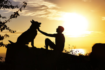 silhouette of man and dog sitting in front of each other on nature, boy caress his pet at sunset