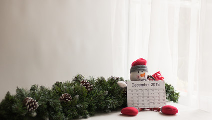 Calendar December 2018, happy Snowman image wears winter clothes and festive green branches of fir tree are in a room with white curtains on a window. Concept: Christmas and New Year's holiday's card.