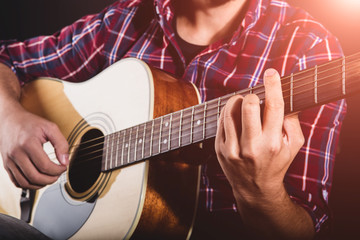 GUITARIST PLAYS ON THE ACOUSTIC GUITAR ON THE STAGE