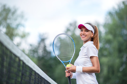 Smiling young girl with a tennis racket