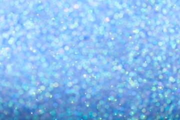 Blurred shiny blue background with sparkling lights.
