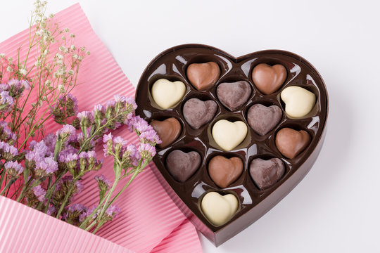 Beautiful flowers with heart shaped box of chocolates on white background