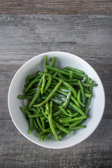 whole green beans with butter in white bowl flat lay