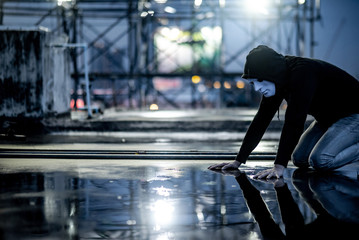 Reflection of mystery hoodie man in white mask feeling guilty looking his face on wet floor while raining. Sadness, depression and surrender concepts