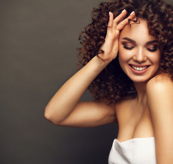Fashion studio portrait of beautiful smiling woman with afro curls hairstyle. Fashion and beauty.