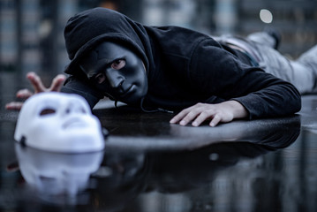 Mystery hoodie man in broken black mask lying in the rain trying to grab white mask on wet floor. Major depressive disorder or bipolar disorder. Depression concept
