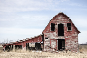 Abandoned Midwest Barn. Weathered and worn red barn on an abandoned farm in the American Midwest.