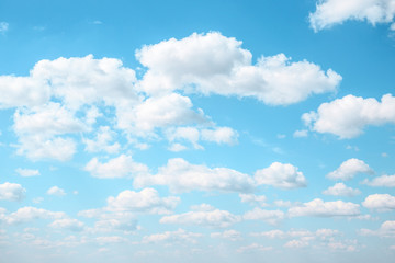 White Fluffy clouds in the light blue sky. Gradient Celestial Azure background. Cloudscape in sunny summer day.