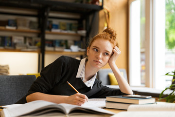 Image of beautiful student studying, while sitting at desk in college library with bookshelf background