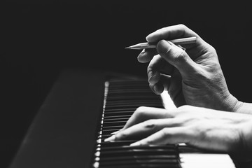 male songwriter hands composing a song on piano, black and white. song writing concept
