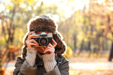Young woman taking pictures in the autumn park. Concept girl photographer