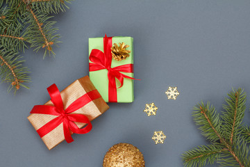 Gift boxes, fir tree branches and christmas toys on gray background