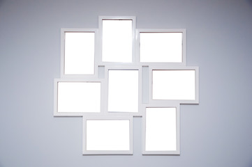 Set of frames on the grey wall with blank photos inside